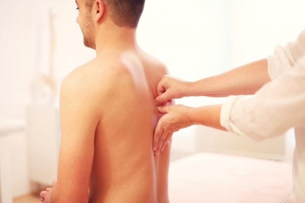 Detailaufnahme einer osteopathischen Behandlung eines Mannes in der Praxis.